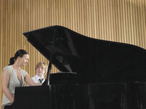 Teacher And Boy Playing Piano In Music Class stock photo
