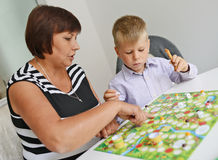 Teacher and boy playing with table game. Royalty Free Stock Photo