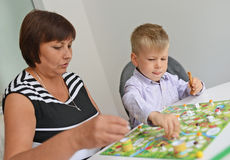 Teacher and boy playing with table game. Stock Photo