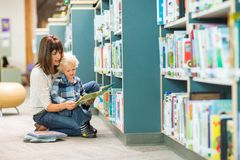 Teacher And Boy Reading Book By Bookshelf Stock Photo