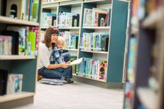 Teacher And Boy Reading Book By Bookshelf Royalty Free Stock Image