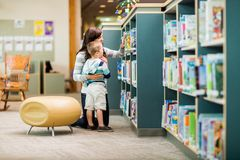 Teacher And Boy Selecting Book In Library Stock Photography