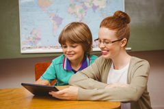 Teacher and boy using digital tablet in classroom Royalty Free Stock Photography