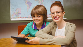 Teacher and boy using digital tablet in classroom. Portrait of female teacher and boy using digital tablet in the classroom Royalty Free Stock Photography