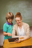 Teacher and boy using digital tablet in classroom. Portrait of female teacher and boy using digital tablet in the classroom Stock Photo