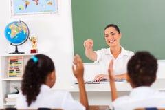 Teacher calling students. Elementary teacher calling students in classroom Stock Photo