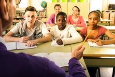 Teacher calls student at far desk to answer. Male teacher calls student at far desk to answer Stock Photos