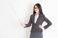 Teacher with cane. Asian female teacher hand holding a cane in class lesson, standing on plain background royalty free stock photography