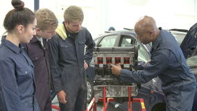 Teacher In Car Mechanic Class Demonstrating How Engine Works stock video footage