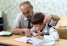 Teacher and careless pupil. The teacher and the pupil studies the alphabet at classroom. Primary school Royalty Free Stock Photo