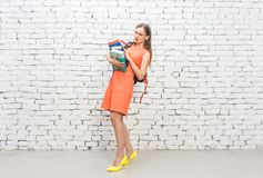 Teacher carrying pile of books to her lesson. Teacher carrying heavy pile of books to her lesson Stock Photos