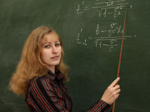 Teacher and chalkboard. Young woman (teacher) are standing with pointer in hand close to chalkboard with formulas Stock Image