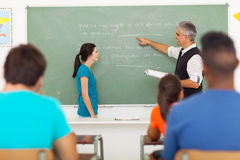 Teacher chalkboard student. Senior teacher pointing at chalkboard with student standing in front of the class Stock Photo