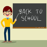Teacher Character Chalkboard. Happy teacher character standing on classroom in front of blackboard pointing at Back to School text Royalty Free Stock Image