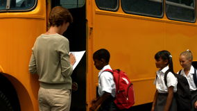 Teacher checking list of pupils by bus stock video