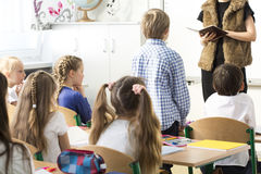 Teacher checking the presence. Elegant teacher checking the pupils' presence during lesson. Little standing by his bend Royalty Free Stock Images