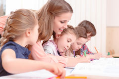 Teacher checking work of pupils Royalty Free Stock Photography