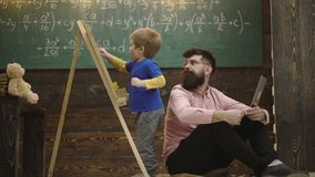 Teacher checks student writing on chalkboard. Pupil talking to his tutor or daddy while solving task. Home education
