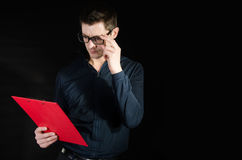 Teacher checks the test. Attractive teacher with red folder reading test Royalty Free Stock Photos