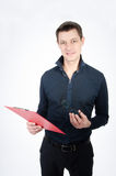 Teacher checks the test. Attractive teacher with red folder reading test Royalty Free Stock Images