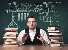 Teacher at chemistry class. A young chemistry teacher in the middle of a chemical process explanation with tubes, reactions drawn on the blackboard back to royalty free stock photo