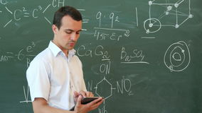 Teacher of chemistry leading lecture from tablet standing in front of the blackboard. Professional shot on Lumix GH4 in with high 4K resolution. You can use it stock video footage