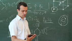 Teacher of chemistry leading lecture from tablet standing in front of the blackboard royalty free stock images