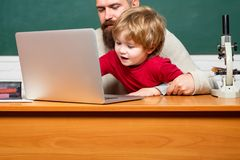 Teacher and child. Happy family - daddy and son together. Chalkboard background. Childhood and parenthood. Dad son are stock image