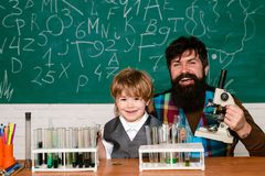 Teacher and child - learning at home. Teacher helping his teen students with chemistry or biology on education class royalty free stock images