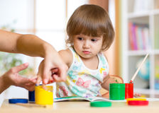 Teacher and child painting together at nursery stock photography