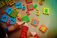 Teacher and child play with number puzzle. Learn calculation Stock Photography