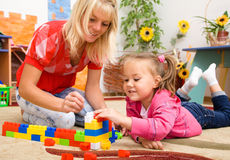 Teacher and child are playing with bricks Royalty Free Stock Photography