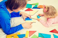 Teacher and child playing with geometric shapes Royalty Free Stock Images