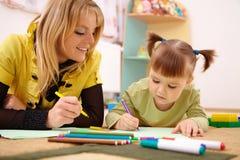 Teacher with child in preschool Stock Photos