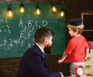 Teacher and child talking in the classroom. Little schoolboy in Oxford cap answering the question in front of the green. Board. Male adult sitting at the desk Stock Images