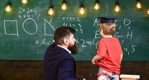 Individual education concept. Teacher and child turned back in the classroom. Boy listening to the explanation about. Teacher and child turned back in the royalty free stock images