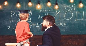 Individual education concept. Teacher and child turned back in the classroom. Boy listening to the explanation about. Teacher and child turned back in the stock photo