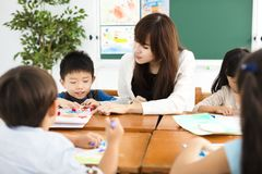 Teacher and children drawing in the classroom. Happy teacher and children drawing in the classroom Stock Images