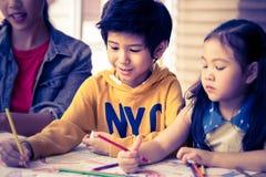 Teacher and children drawing in kindergarten art classroom. Teacher and children are drawing in kindergarten art classroom stock image