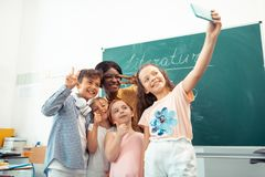 Teacher and children feeling happy while making selfie together stock image