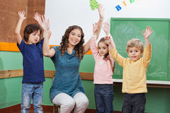 Teacher And Children With Hands Raised In. Portrait of young preschool teacher and children with hands raised in classroom Royalty Free Stock Image