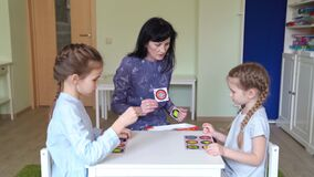 Teacher with children play cards geometric shapes