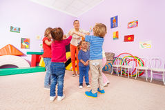 Teacher and children play roundelay around girl Stock Images
