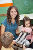 Teacher With Children Playing Xylophone In. Portrait of happy preschool teacher with children playing xylophone in kindergarten Royalty Free Stock Photos