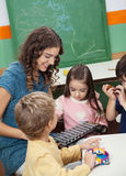 Teacher And Children Playing With Xylophone In. Young preschool teacher and children playing with xylophone in music class Royalty Free Stock Photography