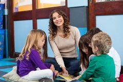 Teacher With Children Reading Book In Classroom. Portrait of young teacher with children reading book while sitting on floor in classroom Stock Photography