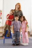 Teacher and children (4-6) standing in classroom, smiling, portrait Stock Image