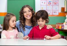 Teacher With Children Using Digital Tablet At Desk. Portrait of young teacher with children using digital tablet at classroom desk Stock Photos