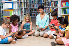 Teacher with children using digital tablet. Female teacher with children using digital tablets in library Stock Photos