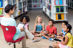 Teacher with children using digital tablets. Female teacher with children using digital tablets in library Royalty Free Stock Photo